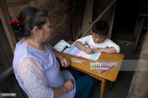 In this picture taken on September 7 a woman helps a boy with his school homework inside their room in a migrant village on the outskirts of Beijing...