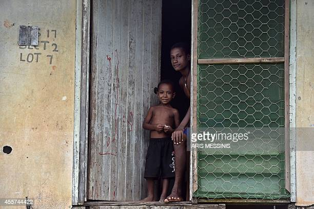 In this picture taken on September 7 a young girl and her brother look on while standing at the door of their house in the town of Kerema AFP PHOTO /...