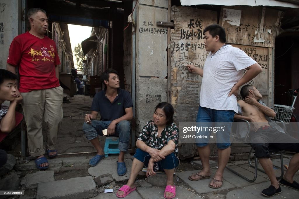 In this picture taken on September 7, 2017, people relax on a street in a migrant village on the outskirts of Beijing. Surrounded by the sleek hi-tech campuses and luxury condominiums of 'Beijing's Silicon Valley', migrants from the countryside recreate village life, cooking in outdoor communal areas, playing cards and showering in the street. But their community's days are numbered. / AFP PHOTO / Nicolas ASFOURI / TO GO WITH China-poverty-migrant, FOCUS