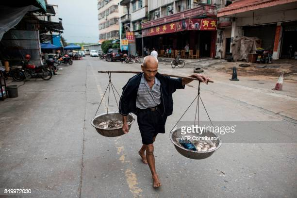 In this picture taken on September 8 a man from the Tanka community walks to a market to sell his fish in Datang southern China's Guangdong province...