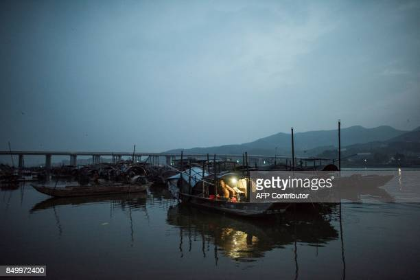 TOPSHOT In this picture taken on September 8 an elderly man from the Tanka community prepares to sleep in his boat moored on a river in Datang...