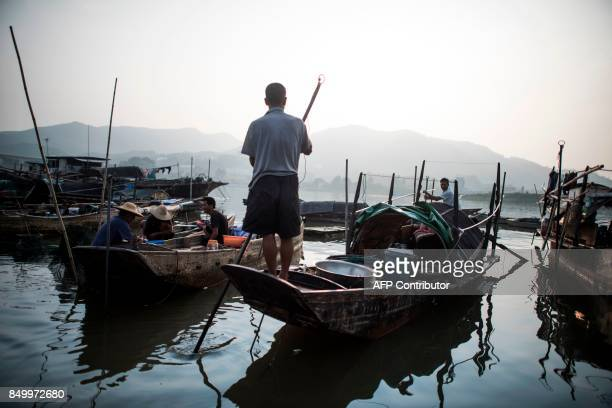 In this picture taken on September 8 people from the Tanka community get in their boats after selling fish in Datang southern China's Guangdong...