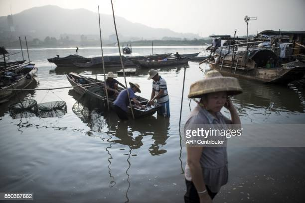 In this picture taken on September 8 people from the Tanka community get in a boat after selling fish in Datang in southern China's Guangdong...