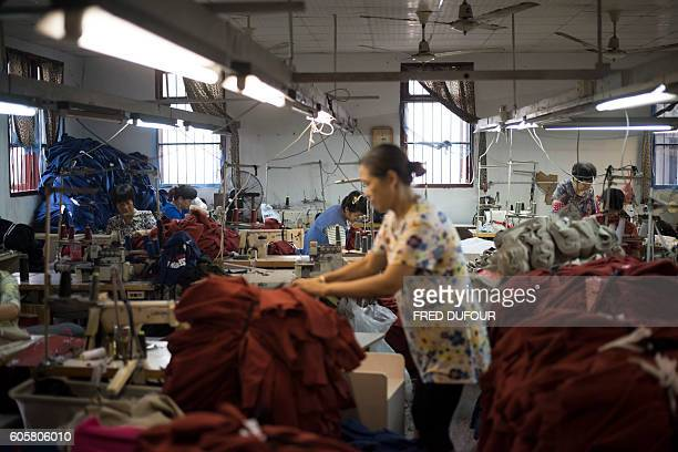 In this picture taken on September 8 workers sew tshirts in a factory in Zhujiajiao on the outskirts of Shanghai / AFP / FRED DUFOUR