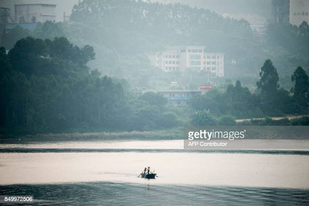 In this picture taken on September 9 two men from the Tanka community fish on a river in Datang southern China's Guangdong province Along southern...