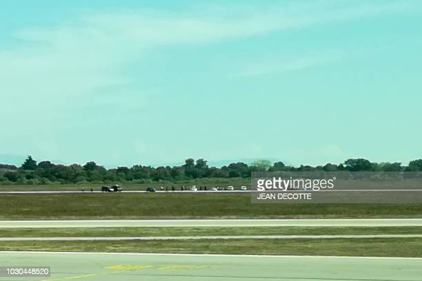 In this picture taken with a mobile phone through the window of a plane shows a French gendarmes and police arresting a man on the tarmac of Lyon's...
