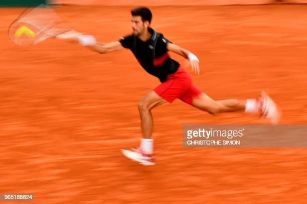 In this picture taken with a slow shutter speed Serbia's Novak Djokovic returns the ball to Spain's Roberto Bautista Agut during their men's singles...
