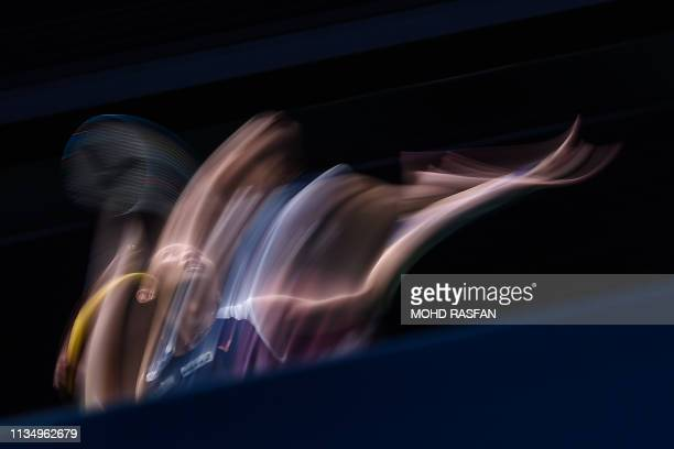 TOPSHOT In this picture taken with slow shutter speed Taiwan's Tai Tzu Ying hits a return against Thailand's Ratchanok Intanon during their women's...