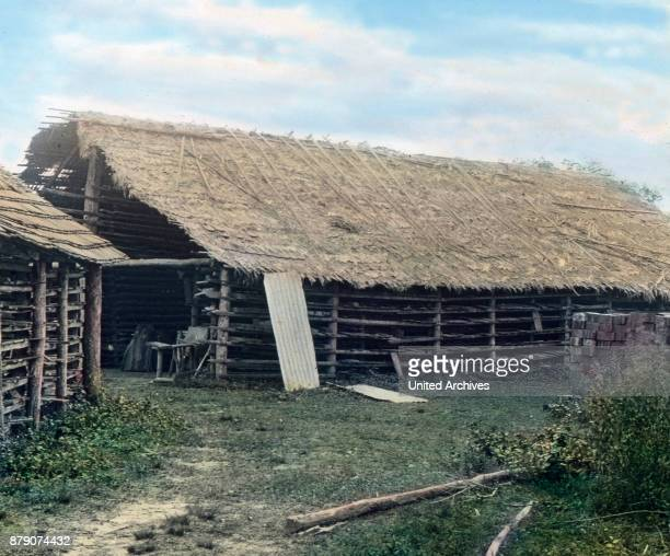 In this picture we see a brickyard middle of the jungle Some resting on piles raw roofs of palm leaves serve as preparation and drying sheds Then the...
