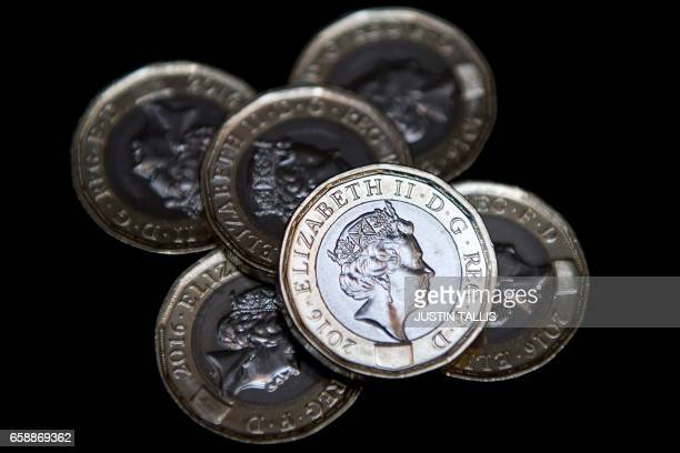 In this posed photograph, newly issued 12-sided £1 coins are pictured in a pile in London on March 28, 2017. Britain's new £1 coin with the symbols...