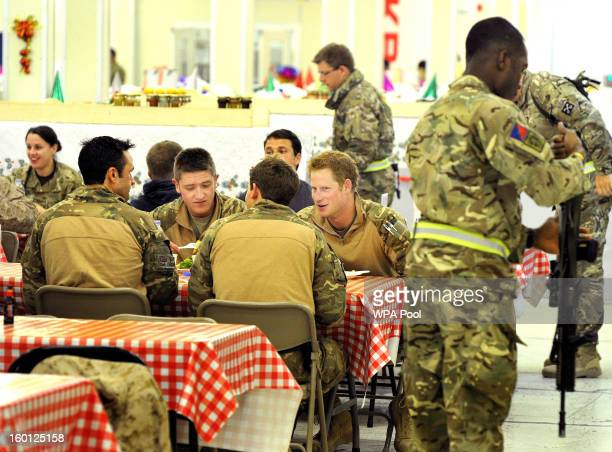 In this previously unissued image released on January 27 Prince Harry sits with his fellow air crew in the DFAC at Camp Bastion on December 11 2012...