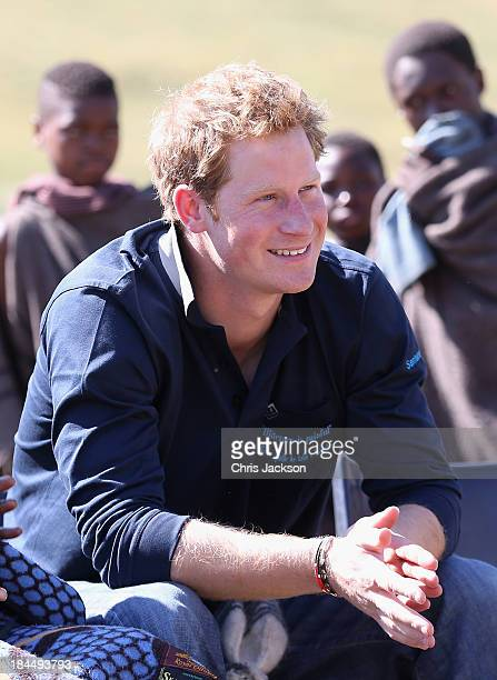 In this previously unreleased photo Prince Harry smiles as he learns about plans to build the new Sentebale Mateanong Herd Boy School during a visit...