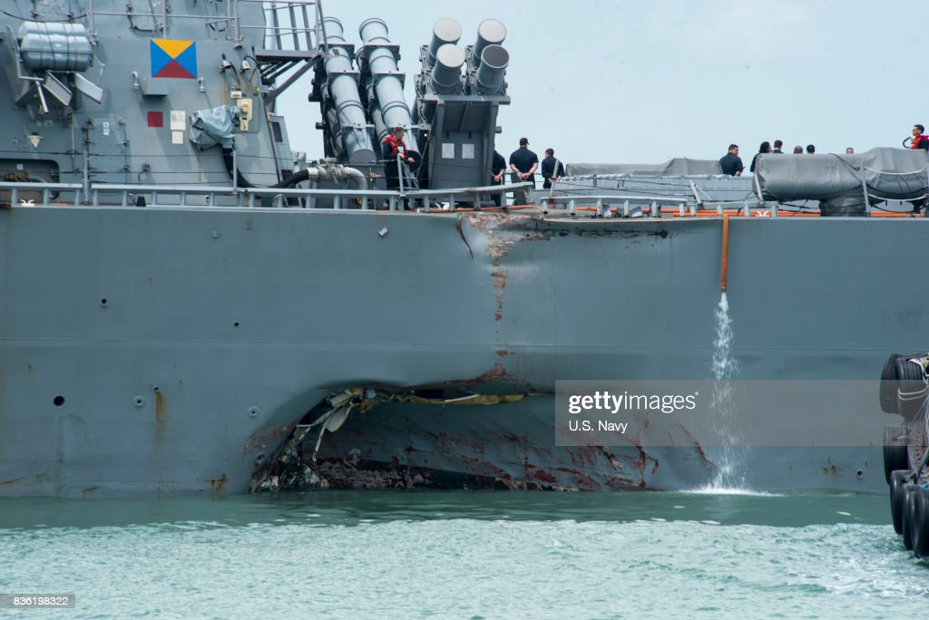 In this released U.S. Navy handout, damage to the portside is visible as the Guided-missile destroyer USS John S. McCain (DDG 56) steers towards Changi Naval Base, Republic of Singapore, following a collision with the merchant vessel Alnic MC while underway east of the Straits of Malacca and Singapore on Aug. 21. Significant damage to the hull resulted in flooding to nearby compartments, including crew berthing, machinery, and communications rooms. Damage control efforts by the crew halted further flooding. The incident will be investigated.