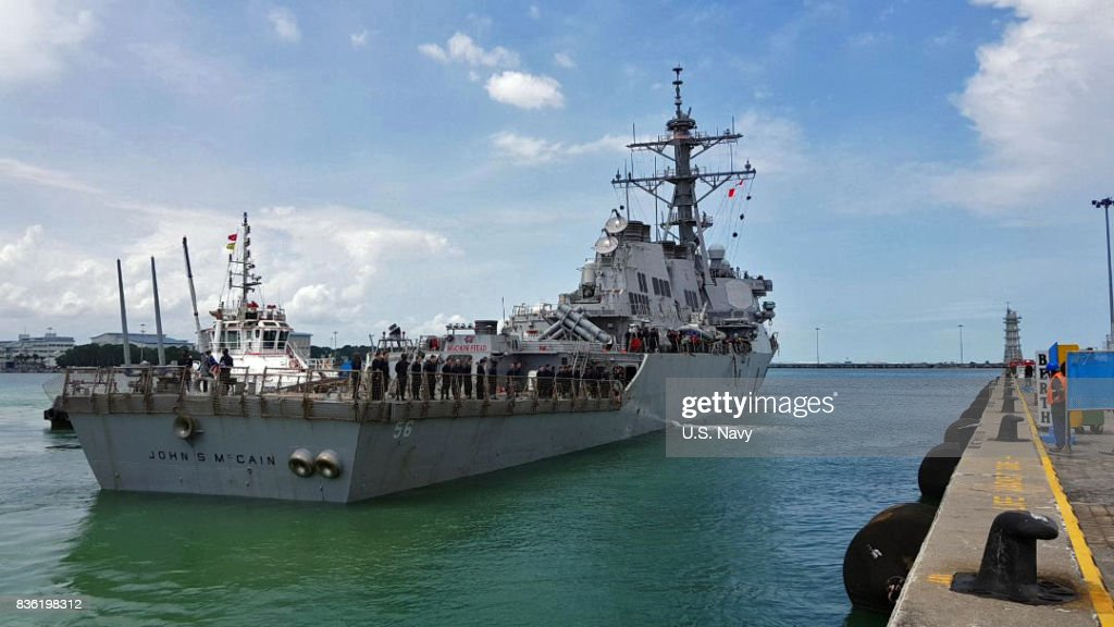 In this released U.S. Navy handout, guided-missile destroyer USS John S. McCain (DDG 56) arrives pier side at Changi Naval Base, Republic of Singapore following a collision with the merchant vessel Alnic MC while underway east of the Straits of Malacca and Singapore on Aug. 21. Significant damage to the hull resulted in flooding to nearby compartments, including crew berthing, machinery, and communications rooms. Damage control efforts by the crew halted further flooding. The incident will be investigated.