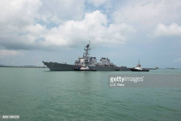 In this released US Navy handout tugboats from Singapore assist the Guidedmissile destroyer USS John S McCain at it steers towards Changi Naval Base...