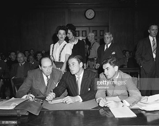 In this remarkable photo actor Errol Flynn confers with attorneys as his accuser in a morals charge Peggy Satterlee night club dancer walks past him...