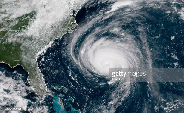 In this satellite image provided by US National Oceanic and Atmospheric Administration Hurricane Florence churns through the Atlantic Ocean toward...