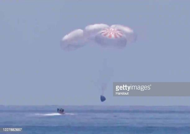 In this screen grab from NASA TV, SpaceX 's Crew Dragon capsule spacecraft just before it splashes down in to the water after completing NASA's...