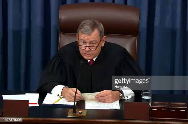 In this screengrab taken from a Senate Television webcast Chief Justice John Roberts reads a question from a senator during impeachment proceedings...