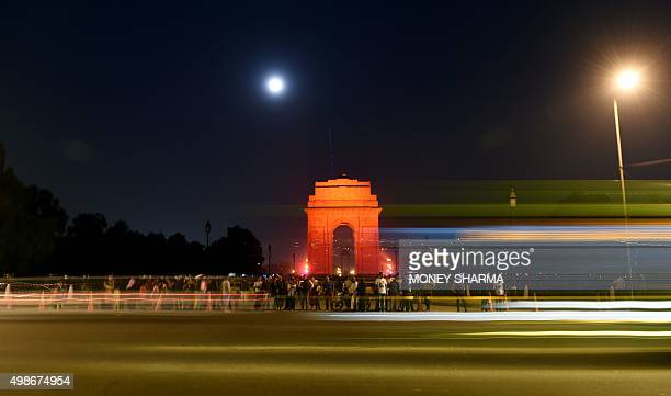 In this slow shutter speed exposure traffic passes by as orange lighting illuminates The India Gate Monument in New Delhi on November 25 on the...