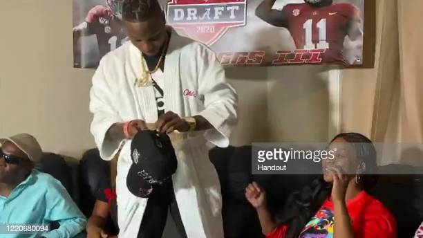 In this still image from video provided by the NFL, Henry Ruggs III, center, gets ready to put on a Las Vegas Raiders cap after being selected by the...