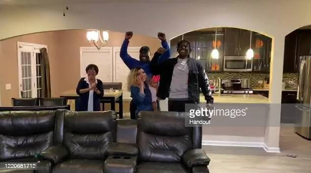 In this still image from video provided by the NFL Javon Kinlaw right celebrates after being selected by the San Francisco 49ers during the first...