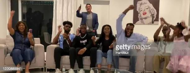 In this still image from video provided by the NFL Josh Uche seated center talks on the phone as he is selected by the New England Patriots during...