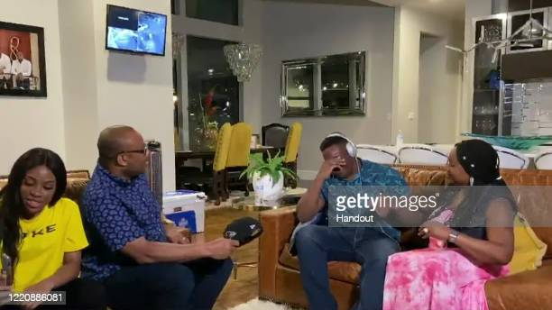 In this still image from video provided by the NFL Justin Madubuike second from right reacts as he is selected by the Baltimore Ravens during the...
