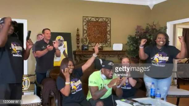 In this still image from video provided by the NFL Patrick Queen seated at front center reacts along with others after being selected by the...