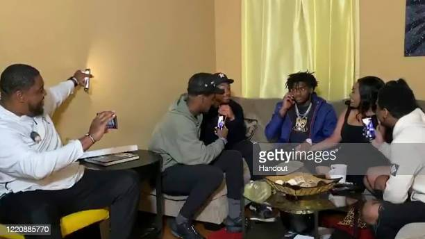 In this still image from video provided by the NFL, Trevon Diggs third from right, talks on the phone as he's selected by the Dallas Cowboys during...
