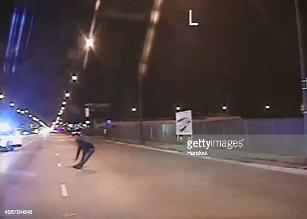 In this still image taken from a police vehicle dash camera relased by the Chicago Police Department on November 24 Laquan McDonald falls to the...