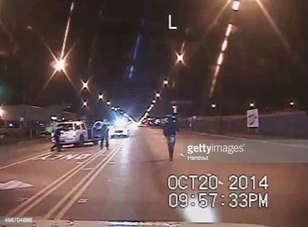 In this still image taken from a police vehicle dash camera released by the Chicago Police Department on November 24 Laquan McDonald walks up a...