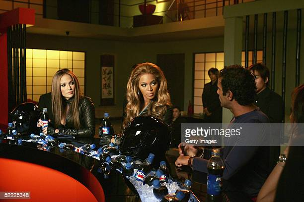 In this still released on February 21 Jennifer Lopez and Beyonce Knowles discuss a scene with director Tarsem Singh during the filming of a new Pepsi...