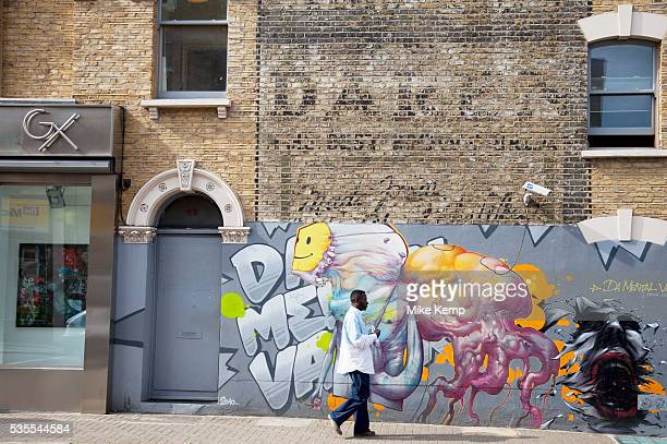 In this street in Camberwell in South London a wall which shows the historic remains of an old advertising sign is contrasted by some modern graffiti...