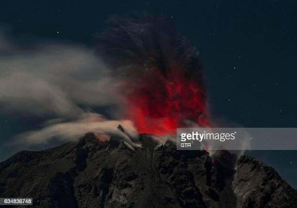 TOPSHOT In this timedexposure night photo taken early on February 12 Mount Sinabung volcano spews reddish smoke and ash as seen from the Karo...