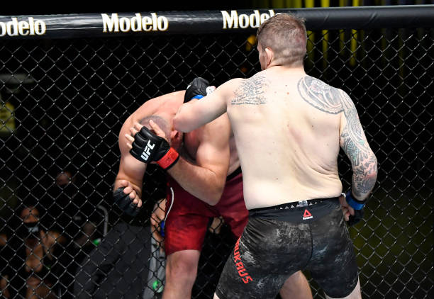 In this UFC handout, Chris Daukaus punches Aleksei Oleinik of Russia in a heavyweight bout during the UFC Fight Night event at UFC APEX on February...