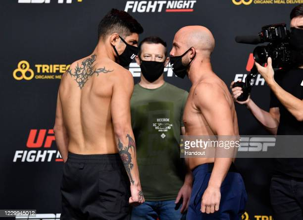 In this UFC handout, Opponents Gabriel Benitez of Mexico and Justin Jaynes face off during the UFC Fight Night weigh-in at UFC APEX on December 04,...