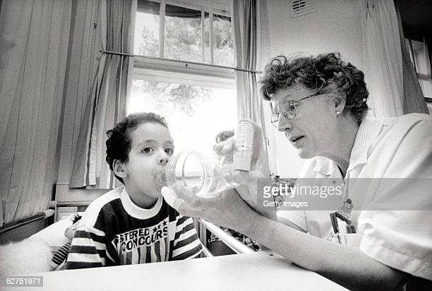 In this undate image a child is helped with an asthma inhaler A report released on May 3 2005 to mark World Asthma Day claims that one person dies...