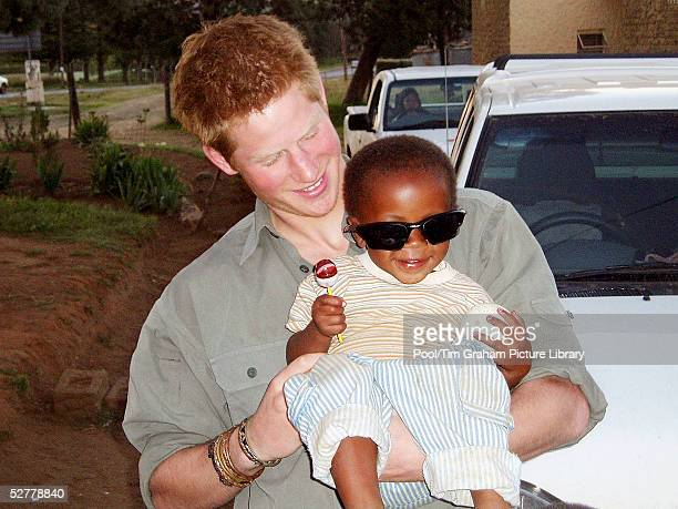 In this undated Clarence House handout photo Prince Harry holds a child from one of the projects being helped by the Lesotho Fund Prince Harry has...
