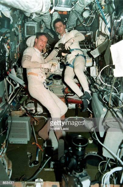 In this undated file photo German astronaut Thomas Reiter left and Russian cosmonaut Yuri Gidzenko prepare an antigravity experiment aboard the...