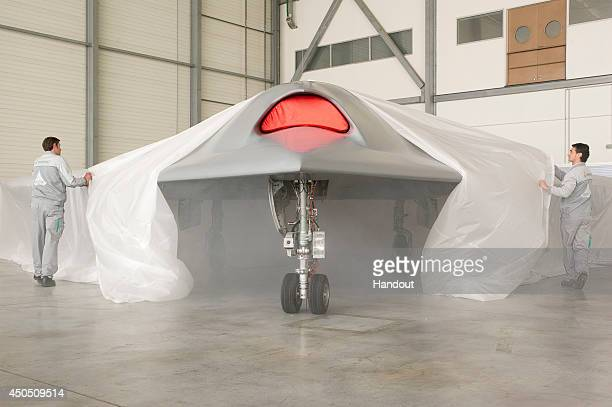In this undated handout image supplied by Dassault Aviation on June 12 Two ground mechanics unveil the nEUROn, an Unmanned Combat Air Vehicle taking...