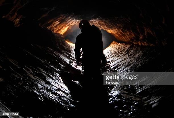 In this undated handout photo a spelunker explores the Riesending cave where an explorer is currently lying injured 1000 meters below since June 8...