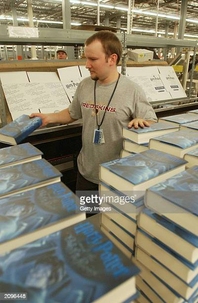 In this undated handout photo Amazoncom employee Chris Schmidt puts copies of 'Harry Potter and the Order of the Phoenix' into a machine that boxes...