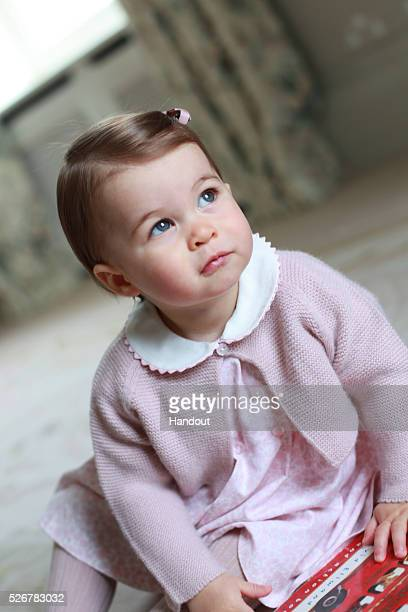 In this undated handout photo provided by HRH The Duke and Duchess of Cambridge released on May 1 Princess Charlotte of Cambridge looks up as her...