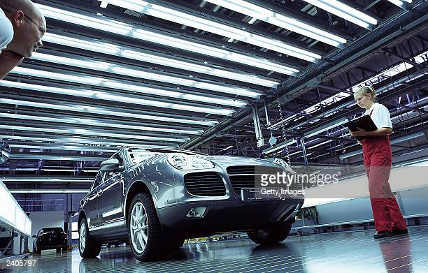 In this undated handout photo provided by Porsche AG workers perform a quality check on a Porsche Cayenne car at the Porsche factory in Leipzig...