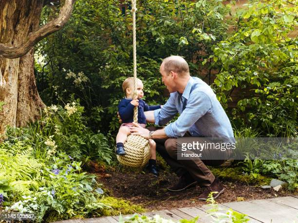 In this undated handout provided by Kensington Palace Prince William Duke of Cambridge and Prince Louis play with a rope swing in the Adam White and...