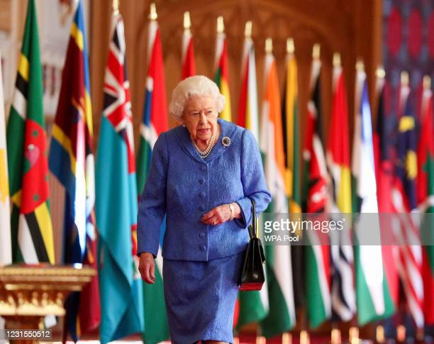 In this undated image released on March 6 Queen Elizabeth II walks past Commonwealth flags in St George's Hall at Windsor Castle, to mark...