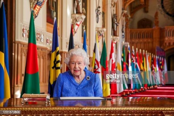 In this undated image released on March 7 Queen Elizabeth II signs her annual Commonwealth Day Message in St George's Hall at Windsor Castle, to mark...