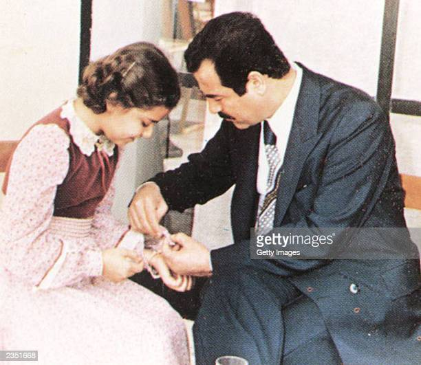 In this undated photo Saddam Hussein helps his daughter Ragad during a visit with family friends on the outskirts of Baghdad Raghad Saddam Hussein...