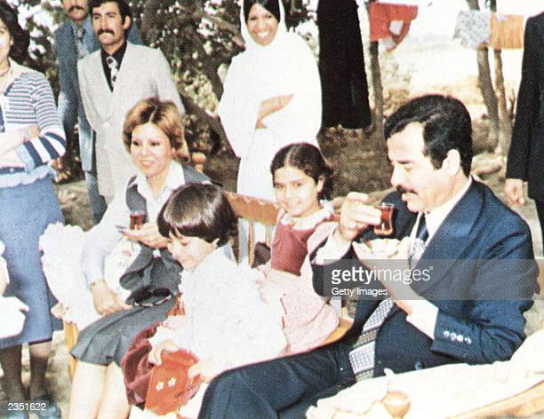 In this undated photo Saddam Hussein his daughters Ragad and Rana and first wife Sajida during a visit with family friends on the outskirts of...